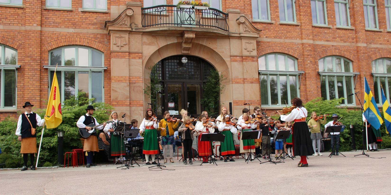 Musikskolans Spelmanslag framträder på nationaldagen vid kommunhuset.